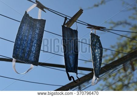 Homemade Community Face Masks From Cloth After Washing To Dry On A Clothesline Backlit Against A Blu