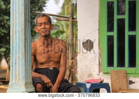 Probolinggo, Indonesia - June 14, 2013: Old Indonesian Man On Porch Of His House In A Village In Jav