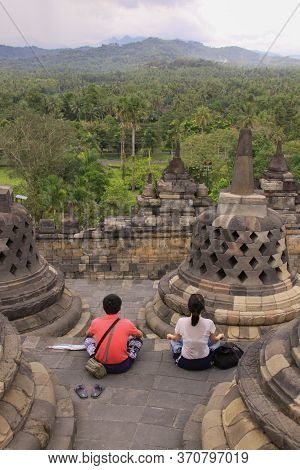 Borobudur, Indonesia - June 10, 2013: Couple Meditate At Borobudur Temple, Java, Indonesia. Candi Bo