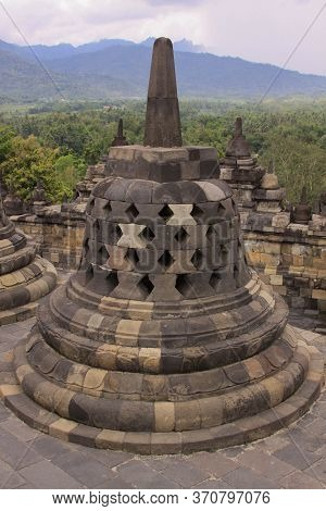 One Stupa In Foreground And Stupas In Background On Top Of Candi Borobudur, The Largest Buddhist Tem