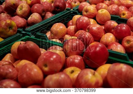 A Bunch Of Ripe Red And Yellow Apples In The Green Containers At The Market. Delicious Fresh Fruits