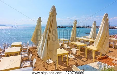 Open-air cafe with tables and umbrellas on the beach in waiting of guests on sunny summer day. Greece