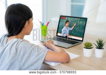 Asian Girl Student Video Conference E-learning With Teacher On Computer In Living Room At Home. Home
