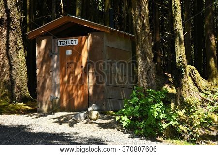 An Image Of An Old Wooden Outdoor Public Toilet In A Wooded Area.