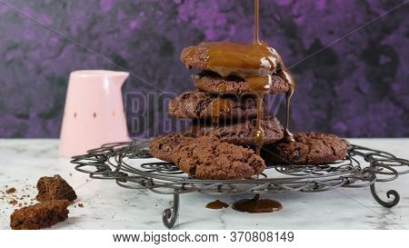 Pouring Extra Chocolate Sauce Over Stack Of Chocolate Chip Homemade Cookies.