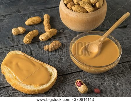 Peanut Butter, A Wooden Bowl With Peanuts And Peanut Fruit On A Wooden Table. Natural Peanut Cream.