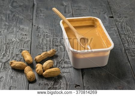 Peanut Beans And A Plastic Box Of Peanut Paste On A Black Wooden Table. Natural Peanut Cream.