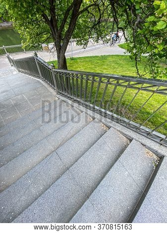 Stone-paved Staircase Down In The Summer Park. Stone Stairway Near Blossoming Tree