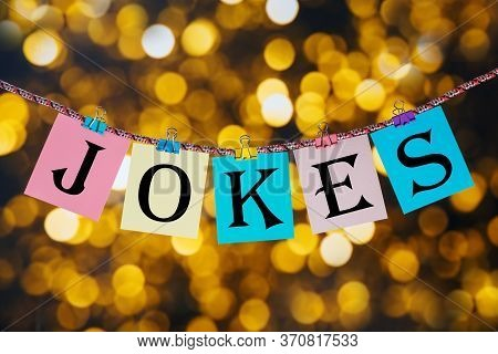 Word Jokes Printed On Clothespin Clipped Cards In Front Of Defocused Glowing Lights