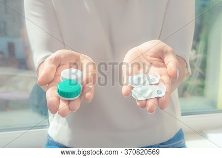 The Woman Gives In The Hands Of One-day Contact Lenses And Reusable Contact Lenses. Choosing The Typ