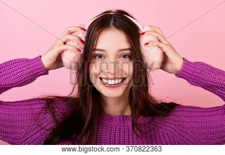 Cute Caucasian Lady In A Knitted Sweater. She Smiles Broadly And Holds Fluffy Pink Winter Headphones