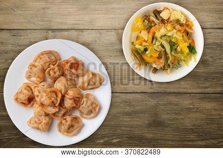 Dumplings On A White Plate On Wooden Background. Dumplings In Tomato Sauce With Salad. Dumplings Top