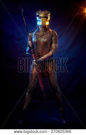 Valkyrie Girl Looking Like An Alien In Shiny Military Armor, A Strange Helmet And A Spear In A Dark