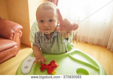 Curious Baby Sitting In Highchair In Cozy Living Room. Little Child Playing Toy Plane Pointing Finge
