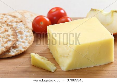A wedge of English Cheddar cheese with crackers and cherry tomatoes on a cheeseboard