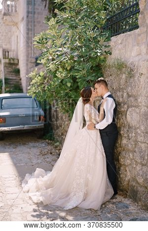 A Wedding Couple Hugs On The Streets Of The Old City, In The Shade Of A Fig Tree, Against The Backgr