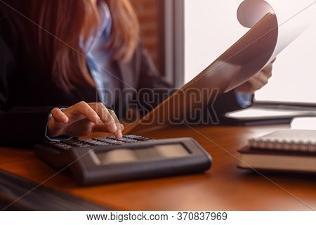Business Women  Working With Calculator And  Business Document On Office Table In Office. Finance Ac