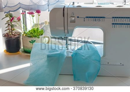 Handmade Sew The Face Mask Against Coronavirus Disease Covid-19 Pandemia. Sewing Machine With Spunbo