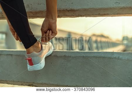 Woman Tying Shoe Laces In The Morning.