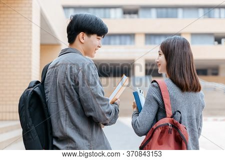 High School Students Hold Book And Laptop Talking And Laughing In A Hallway Between Classes