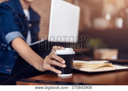 Young Woman Sitting On Sofa At Coffee Shop And  Drinking Coffee While Working On Laptop.