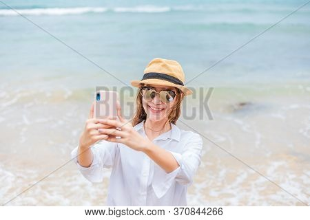 Happy Young Women Wearing  Sun Glasses Use Mobile Phones To Take Pictures On The Beach While Traveli