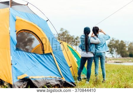 A Group Of Friends Travel And Camping Near Lake And Mountain Back.