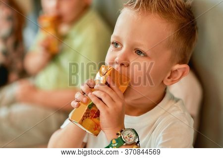 Enjoying A Drink. Portrait Of A Cute And Stylish Little Boy In White T-shirt Drinking Juice After In