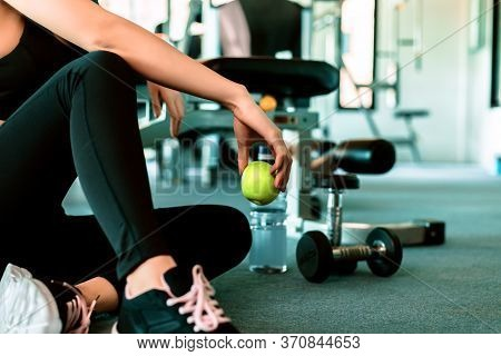 Woman Exercise In Gym Fitness Breaking And Relax. Hand  Holding Apple Fruit After Training Sport And