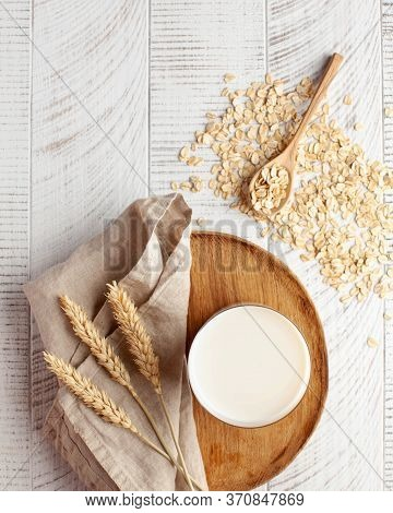 Oat Milk In A Glass, Flakes Of Baked Cereals. Milk Substitute, Milk For Vegetarians. Flatlay. Copy S