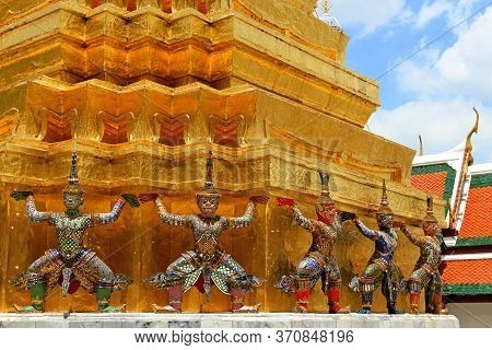 The Ramayana Giant Statues Are Standing With Big Golden Pagoda Background At Wat Ph-ra Kaew Ancient