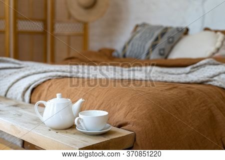 Close Up Of Breakfast Tray With Teapot And Cup Against Blurred Background With Hygge Bedroom, Fabric