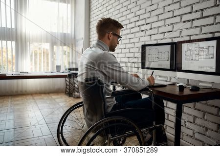 Young Male Engineer Or Architect Using Stylus Pen And Digital Tablet While Sitting At His Workplace.