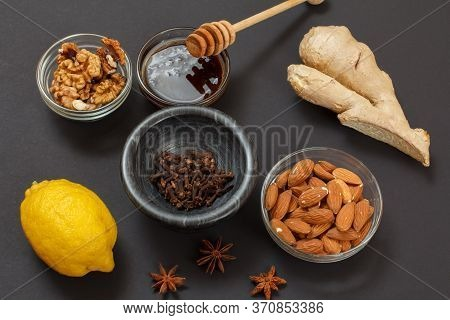Health Remedy Foods For Cold And Flu Relief With Lemon, Ginger, Honey, Almond And Walnuts On A Black