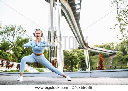 Girl Is Warming Up Before Workout Outdoors, She Is In Trendy Sportswear With A Headphone On Her Head