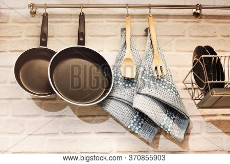 Stainless Railing With Frying Pans And Wooden Utensils With Towels Above Counter With Brick Wall In