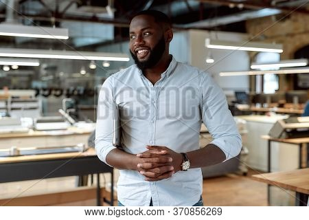 Portrait Of Cheerful African American Businessman Wearing Shirt Looking Aside And Holding Laptop Und