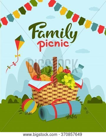 Family Picnic Concept. Wicker Picnic Basket Full Of Healthy Food, Picnic Blanket, Kite, Ball On Gras
