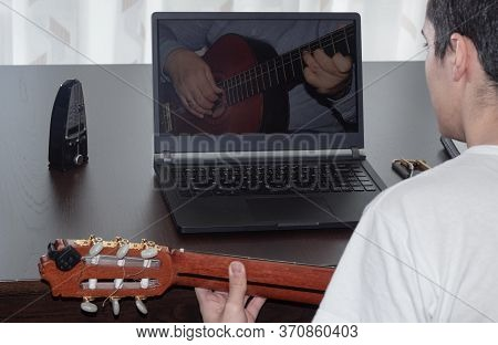 Young Person Doing And Consulting The Online Spanish Guitar Course At Home, With The Metronome And L