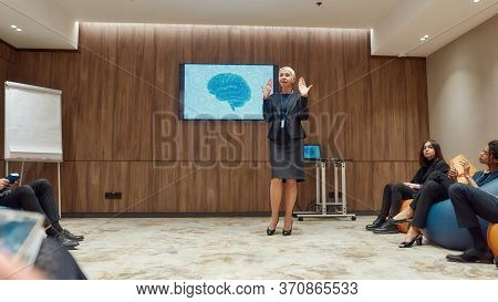 Full-length Shot Of Middle-aged Female Speaker Giving A Talk At Informal Meeting In Modern Workspace