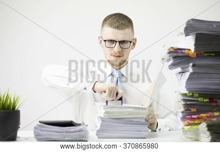 Office Worker In Business Clothes Sits At Table Littered With Papers, Stamps On Stack Of Documents.