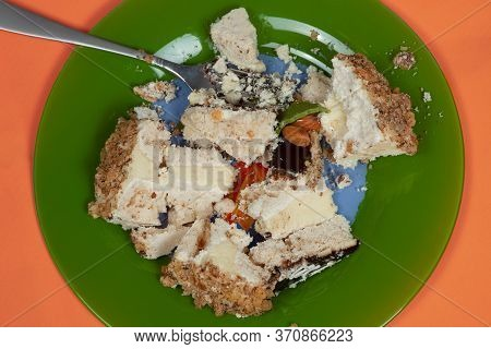 Big Piece Of Cream Cake Crashed In The Green Plate With Fork. Anti Diet Concept, Unhealthy Dessert,