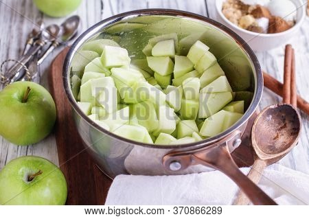 Freshly Diced Granny Smith Green Apples In A Sauce Pan With Ingredients Of Spices And Sugar Lying Ne