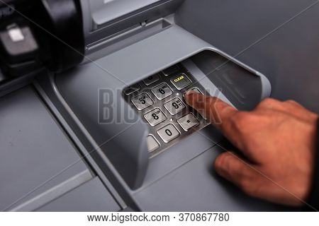 Close Up Of Male Hand Entering Personal Identification Number At An Atm Machine To Withdraw Cash. Cl