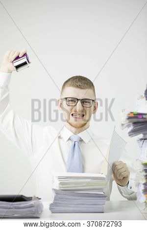Angry Burnout Office Worker Sits At Table Littered With Papers, Stamps On Stack Of Documents. Young