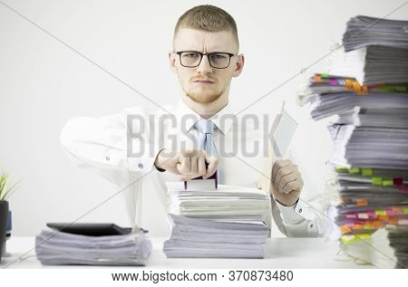 Concentrated Office Worker In Shirt, Tie And Glasses Sits At Table Littered With Papers, Stamps On S