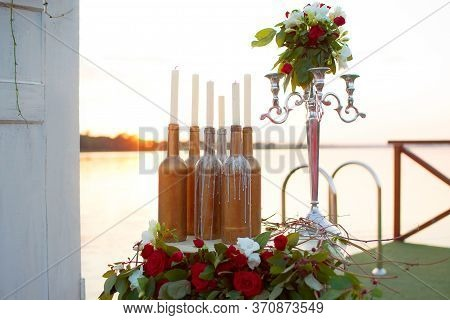 Wedding Decor - Beautiful Installation At The Table By The Sea: Candles, Bottles, Statuette.