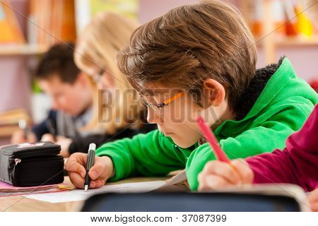 Education - Pupils at primary or elementary school doing their homework or having a school test poster