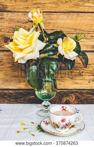 Tea Time: Delicate Cup Of Tea And Yelow Roses On Wooden Background