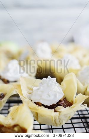 Mini Apple Pies With Phyllo Crust With Whipped Cream On A Bakers Rack. Selective Focus With Blurred